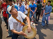 "04 APRIL 2015 - CHIANG MAI, CHIANG MAI, THAILAND: A man plays drums and dances during the Poi Sang Long Festival in Chiang Mai. The Poi Sang Long Festival (also called Poy Sang Long) is an ordination ceremony for Tai (also and commonly called Shan, though they prefer Tai) boys in the Shan State of Myanmar (Burma) and in Shan communities in western Thailand. Most Tai boys go into the monastery as novice monks at some point between the ages of seven and fourteen. This year seven boys were ordained at the Poi Sang Long ceremony at Wat Pa Pao in Chiang Mai. Poy Song Long is Tai (Shan) for ""Festival of the Jewel (or Crystal) Sons.      PHOTO BY JACK KURTZ"