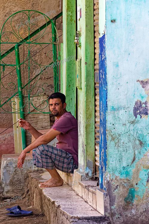 Farm labourer taking a cigarette break outside the doorway of a house on Geziret Al Dahab Island in Cairo