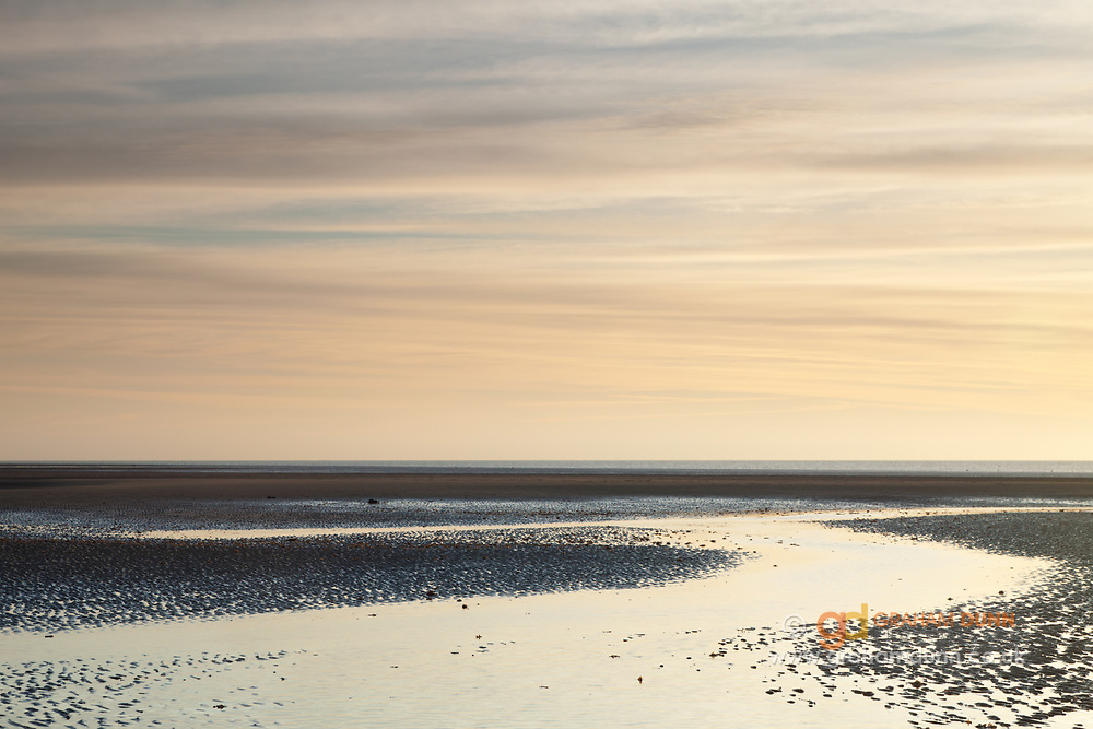 Sublte colours reflect in the low tide waters at Old Hunstanton on North Norfolk's west coast. East Anglia.