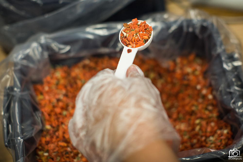 """Dried vegetables are scooped into individual bags with soy and rice during the Stop Hunger Now Foundation's """"Mayday, Mayday"""" food-packing event at SanDisk Corporation in Milpitas, California, on May 13, 2014. (Stan Olszewski/SOSKIphoto)"""