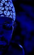 Portrait of half face of man wearing a glowing skull head wrap.Black light