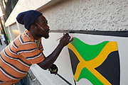 Rastafarian man painting a Jamaican flag on a wall, Kingston.