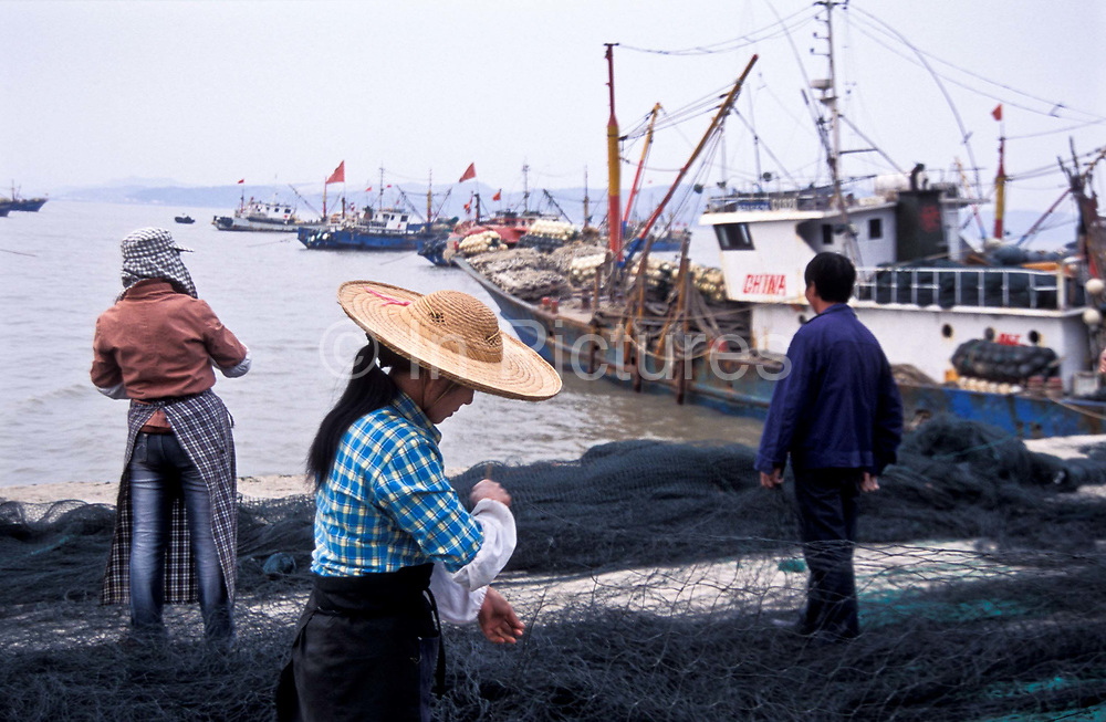 Villagers repair nets in the harbour of Jin Shan Island, China