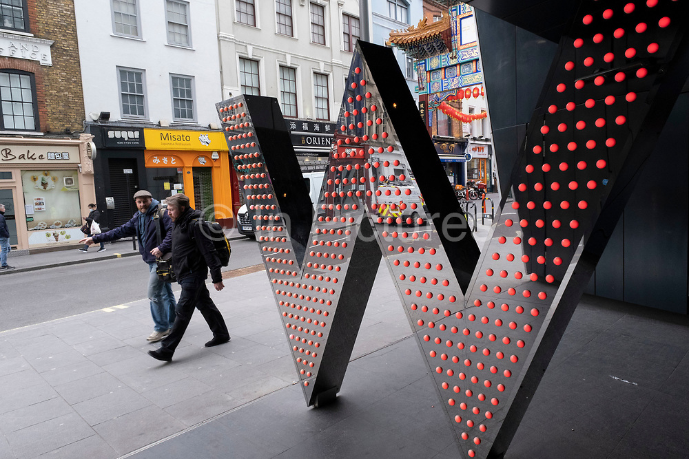 People passing the entrance to the W Hotel on 5th March 2021 in London, England, United Kingdom. This hotel chain provides an exclusive chic and boutique experience for their customers.