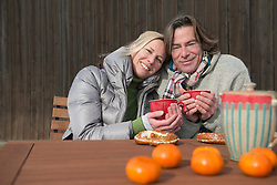 Portrait of couple having tea and snack outdoors, smiling, Bavaria, Germany