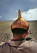 Mongolian wrestler wearing a typical wrestling hat is on his way to a match on his motorcycle.<br /> Near Moron town, Khövsgöl province.