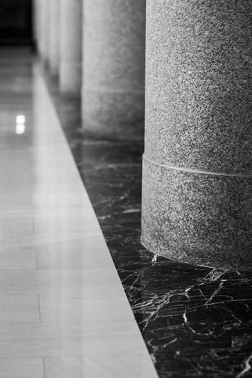 Marble pillars and floor in a chapel rendered in black and white.