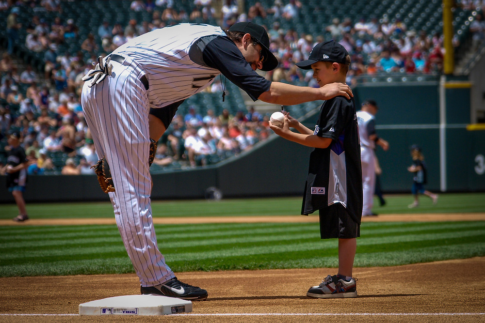 Colorado Rockies first baseman TODD HELTON #17 greets a young fan before a 6-2 victory over the Minnesota Twins in MLB action.