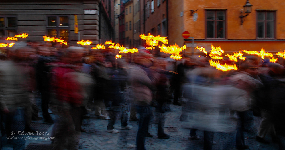 Hundreds carry torches to light a massive bonfire next to the sea in Stockholm.