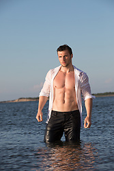 good looking man in wet clothes standing in water