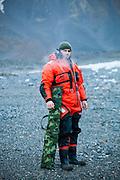 Station cook Dominik Petelski smokes a cigarette on the beach outside the Polish Polar Station, Hornsund, Svalbard.