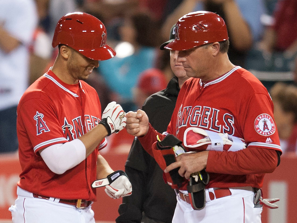 The Angels' Andrelton Simmons gets a fist bump from first base coach Gary Disarcina after his RBI single in the fifth inning Wednesday night at Angel Stadium.<br /> <br /> <br /> ///ADDITIONAL INFO:   <br /> <br /> angels.0616.kjs  ---  Photo by KEVIN SULLIVAN / Orange County Register  -- 6/15/16<br /> <br /> The Los Angeles Angels take on the Minnesota Twins Wednesday at Angel Stadium.