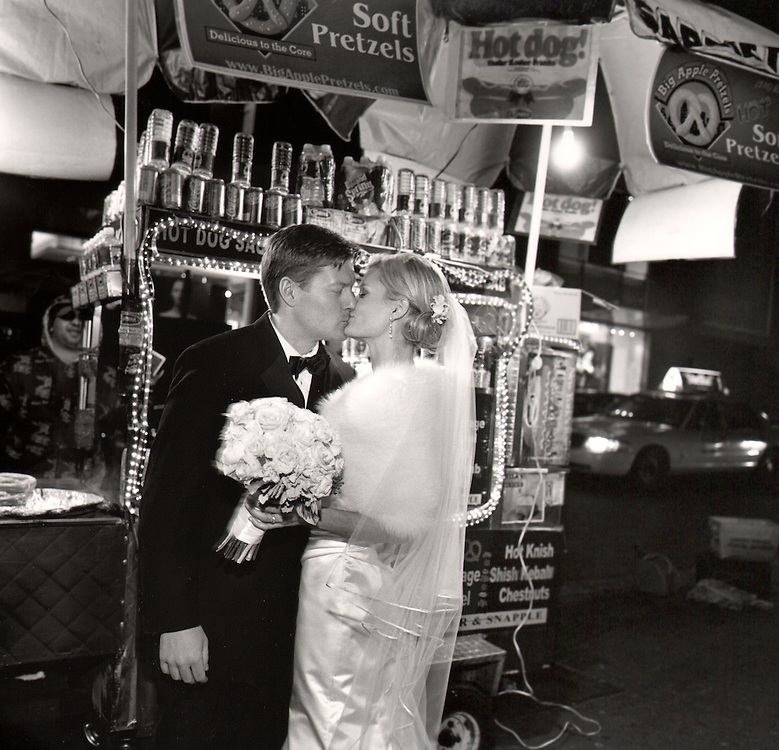 Bride and groom Kiss at night in front of a street vendor food cart on a Manhattan sidewalk, in winter, in a black and white photo