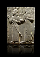 """Hittite monumental relief sculpted orthostat stone panel of Royal Buttress. Basalt, Karkamıs, (Kargamıs), Carchemish (Karkemish), 900-700 B.C. Anatolian Civilisations Museum, Ankara, Turkey.<br /> <br /> King Araras holds his son Kamanis from the wrist. King carries a sceptre in his hand and a sword at his waist while the prince leans on a stick and carries a sword on his shoulder. <br /> <br /> Hieroglyphs reads; """"This is Kamanis and his siblings. I held his hand and despite the fact that he is a child, I located him on the temple. This is Yariris' image"""".  <br /> <br /> Against a black background. .<br />  <br /> If you prefer to buy from our ALAMY STOCK LIBRARY page at https://www.alamy.com/portfolio/paul-williams-funkystock/hittite-art-antiquities.html  - Type  Karkamıs in LOWER SEARCH WITHIN GALLERY box. Refine search by adding background colour, place, museum etc.<br /> <br /> Visit our HITTITE PHOTO COLLECTIONS for more photos to download or buy as wall art prints https://funkystock.photoshelter.com/gallery-collection/The-Hittites-Art-Artefacts-Antiquities-Historic-Sites-Pictures-Images-of/C0000NUBSMhSc3Oo"""