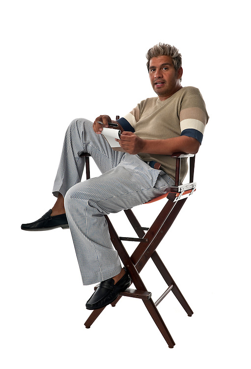 Young and trendy man seated on director chairs taking notes.