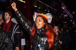 London, November 26th 2014. A vigil for teenager Mike Brown who was shot dead by a policeman in Ferguson, Missouri this year, takes place outside the US embassy in London. Anti-racism and human rights campaigners called the 'emergency' protest following a court verdict that clears Police Officer Darren Wilson of murder. PICTURED: A woman chants slogans as the anti-police-racism march proceeds down Oxford Street.