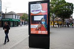 Hounslow, UK. 11th June, 2021. Local residents pass a London Borough of Hounslow Covid-19 public information display amid rising concern regarding the spread of the Delta variant. Hounslow has been identified as a hotspot for the Delta variant first identified in India and both surge testing and increased vaccination have been introduced as counter-measures.