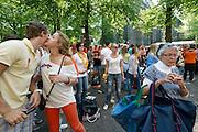 Een oudere vrouw baant zich een weg door het feestgedruis op het Janskerkhof. In Utrecht wordt volop Koninginnedag gevierd met een vrijmarkt, bandjes, bootjes en gewoon lekker liggen in de zon.<br /> <br /> An elder woman is trying to find her way at the crowd at Janskerkhof, while two young people are kissing hello at Queenday.