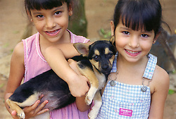 Young Cuban girls holding a pet dog and smiling,