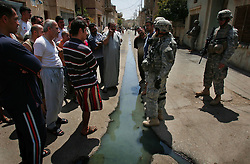 Lt. Col. John Norris, battalion commander for 4th Battalion 23rd Infantry Regiment 172nd Stryker Brigade, (center-right) works to cross divides of language and trust by speaking with area residents to explain the goals of a sweep of the Sunni Baghdad district of Ahdamiyah on Tuesday August 29, 2006. The 172nd was extended at the last moment - with portions of the brigade already back in the States - when they were called upon to bolster security forces in Baghdad seeking to get a handle on a massive wave of sectarian killings in the Iraqi capital.