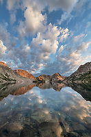 Morning clouds mirrored in still waters of Sawtooth Lake. Sawtooth Mountains Wilderness Idaho