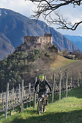 Mountain biker on the move with ruin structure in background,