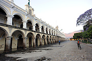 Early morning commuters cycle over the cobbles of  Calle in front of  of the 18th century El Ayuntamiento, the town hall, building on the north side of Parque Central. Antigua Guatemala, Republic of Guatemala. 03Mar14