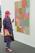 New York, NY - 6 May 2016. Frieze New York art fair. A woman wearing a colorful coat and cap takes photo of Barry McGee's untitled acrylic painting in the Cheim & Reid Gallery.