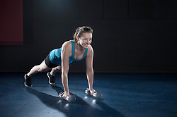 Sportive young woman doing exercise with dumbbell in the gym, Bavaria, Germany