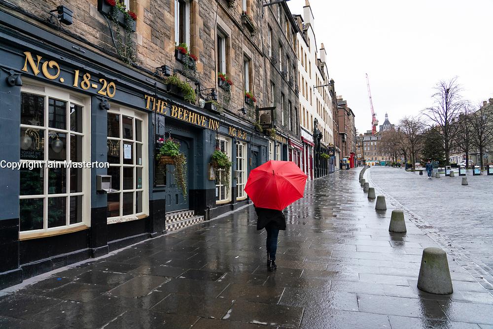 Woman holding red umbrella in rain in The Grassmarket in Old Town of Edinburgh, Scotland, UK