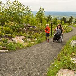 A woman in a wheelchair and her son explore an accessible trail near the summit of Mount Agamenticus in York, Maine.