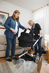 Mother with pregnant daughter looking at new pram..