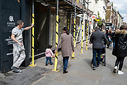 Worker wearing dirty paint covered overalls having a cigarette break in the upmarket area of Chelsea as people pass by on 14th April 2021 in London, United Kingdom. Chelsea is one of the principal areas for exclusive, luxury goods in West London. It is known as a district where the rich and wealthy shop, mostly for high street and high end fashion and jewellery.
