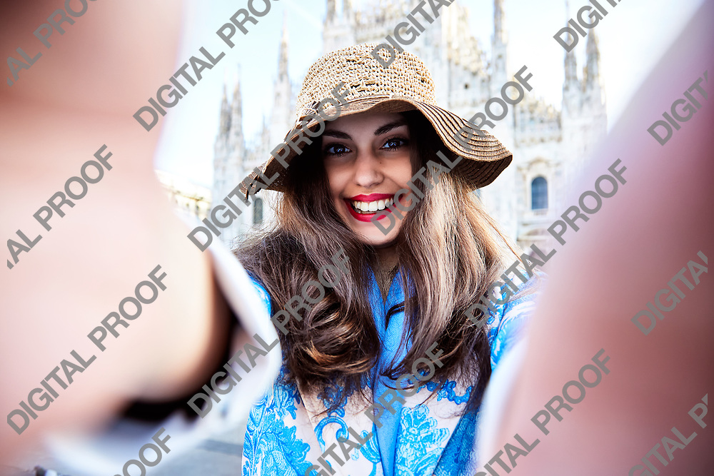 Smiling woman takes a selfie in front of Duomo of Milan, Italy during the day