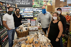 """South Africa - Plettenberg Bay - 8 May 2020 - Pictured left to right is Morné Rheeder and Mariska Rheeder of Zanzos, Duncan Brown of Kwikspar, and Emmy-Lou Mills and Brent Mills, of ROOST cafe. The Kwikspar in Plettenberg Bay, Beacon Isle KWIKSPAR, owned by Duncan Brown, has set up a special table to promote and sell products from local businesses that are unable to trade under the lockdown regulations. A sign on the table reads """"Support our Local Businesses. All items on this table are supplied by local restaurants. They are still unable to welcome you into their businesses. Kwikspar will not add any markup to these products, and all sales will go directly to them."""" South Africa is currently under lockdown in an attempt to flatten the curve to halt the spread of the COVID-19 coronavirus pandemic. Picture: David Ritchie/African News Agency(ANA)"""