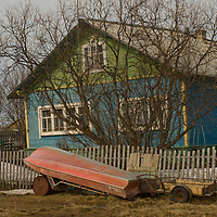 North of the Arctic Circle in Russia,  a boat sits in front of a colorful house in Snopa village, close to the Arctic Ocean coast.
