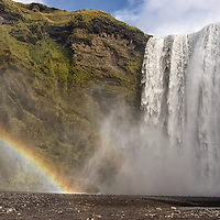 """According to """"Wikipedia"""" - The Skógafoss is one of the biggest waterfalls in the country with a width of 25 metres (82 feet) and a drop of 60 m (200 ft). Due to the amount of spray the waterfall consistently produces, a single or double rainbow is normally visible on sunny days. According to legend, the first Viking settler in the area, Þrasi Þórólfsson, buried a treasure in a cave behind the waterfall. A local boy found the chest years later, but was only able to grasp the ring on the side of the chest before it disappeared again."""