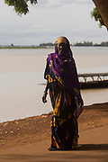 A woman strolling on the riverside on a sunday afternoon. At the confluence of the Niger and the Bani rivers, between Timbuktu and Ségou, Mopti is the second largest city in Mali, and the hub for commerce and tourism in this west-african landlocked country.
