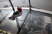 A young girl poses for photos while laying down on the glass viewing deck of the Pearl Oriental TV Tower in Shanghai, China on 23 November 2009.