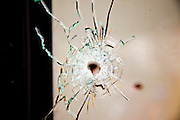 18 MAY 2010 - BANGKOK, THAILAND:  A bullet hole in the window of a coffee shop in Din Daeng Intersection in Bangkok. Witnesses said the coffee shop was hit by sniper fire Monday. Violent unrest continued in Bangkok again Tuesday nearly a week after Thai troops started firing on protesters and Bangkok residents took to the streets in violent protest against the government. Tuesday was not as violent as previous days however. Although protesters continued to set up roadblocks and flaming tire barricades across parts of the city, there was not as much gunfire from the government lines. The most active protesters were at the Din Daeng Intersection about a mile from the Red Shirts' Ratchaprasong camp.  PHOTO BY JACK KURTZ