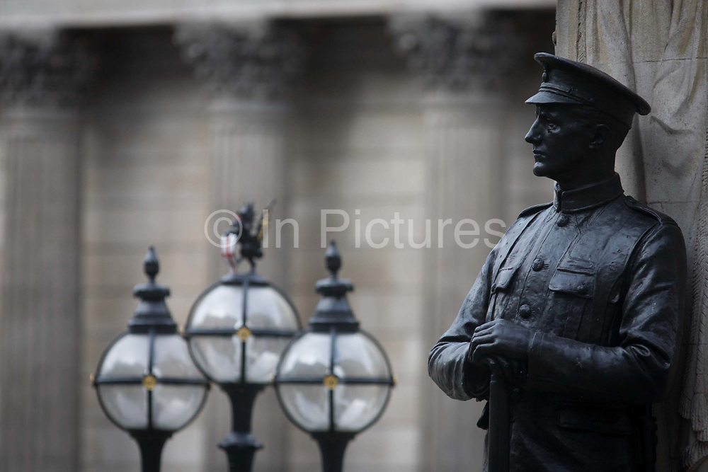 In the 100th year after WW1 started, a detail of the war memorial hero in Cornhill, City of London remembering those killed in the First World War, lost in the trenches and the fields of Flanders from 1914-19. Three lanterns stand to the left and in the background are the pillars of the Bank of England, from where many served in the British forces and now dedicated by the City of London, the UK capital's financial and historic heart. Two soldiers face away from each other with rifles between their boots, they represent a lost generation when the nation's youth sacrificed their lives in the 20th century's first great conflict. The inscription says that their names will live for evermore.