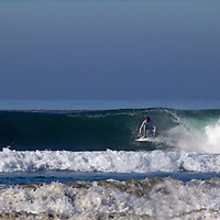 USA, California, San Diego. Surfer emerges brom barrel at Cardiff by the Sea.