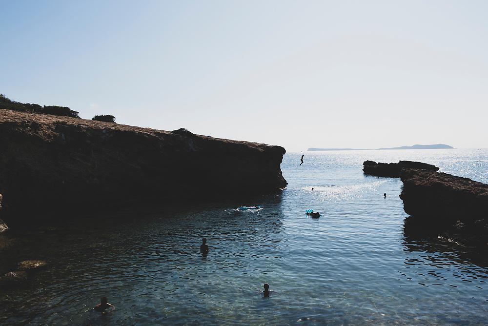 Cala Gració, Ibiza, Spain - July 30, 2018: A man leaps off a cliff into the sea at Cala Gració, Ibiza, Spain.