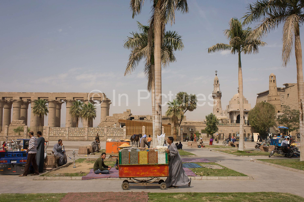 A nuts and seeds stallholder pushes his cart towards arriving tourists in front of the ancient Egyptian columns of Luxor Temple, Luxor, Nile Valley, Egypt. But stallholders await more visitors during the tourist downturn. According to the country's Ministry of Tourism, European visitors to Egypt is down by up to 80% in 2016 from the suspension of flights after the downing of the Russian airliner in Oct 2015. Euro-tourism accounts for 27% of the total flow and in total, tourism accounts for 11.3% of Egypt's GDP. The temple was built by Amenhotep III, completed by Tutankhamun then added to by Rameses II. Towards the rear is a granite shrine dedicated to Alexander the Great and in another part, was a Roman encampment. The temple has been in almost continuous use as a place of worship right up to the present day.