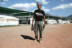 October 5, 2016 - Athens, Greece - An Afghan man infront of UNHCR tents set in a sports facility at Helliniko Olympic complex in Athens, Greece on October 5, 2016Almost 2,500 migrants and refugees, mainly Afghani, are housed at the former Athens airport site, and to an olympic complex used in the 2004 Olympics. In total 60.736 refugees and other migrants are stranded in Greece. (Credit Image: © Panayiotis Tzamaros/NurPhoto via ZUMA Press)