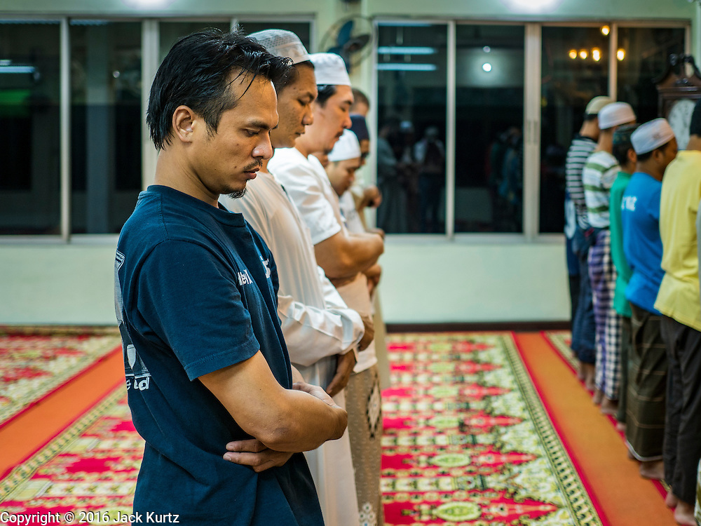 05 JUNE 2016 - BANGKOK, THAILAND:  Men pray at Masjid Darul Faha, a small mosque in the Muslim majority neighborhood of Ban Krua in Bangkok on the night before the start of Ramadan. Ramadan is the ninth month of the Islamic calendar, and starts on June 6 this year. It is observed by Muslims worldwide as a month of fasting to commemorate the first revelation of the Quran to Muhammad according to Islamic belief. This annual observance is regarded as one of the Five Pillars of Islam. Islam is the second largest religion in Thailand.        PHOTO BY JACK KURTZ