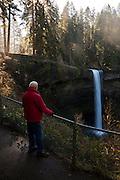 USA, Oregon, Silver Falls State Park, hiker looking at South Falls, MR