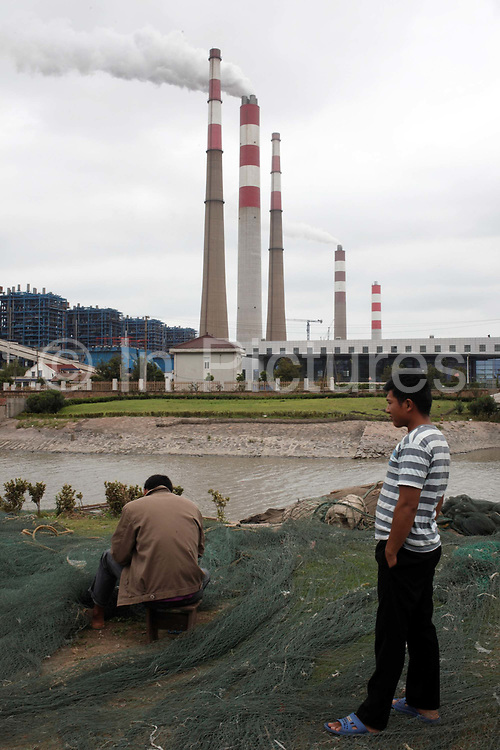 Two fishermen tend to their nets near a large coal firing power plant in Shanghai, China on August 30th, 2009. China is quickly pushing to expand its alternative energy options while currently a majority of its rapidly expanding appetite for electricity is satisfied by coal, which the country has an abundant supply of.