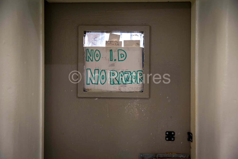 'No ID No Razor' sign in the window of the Prison Officers office in a Wing in Her Majesty's Prison Pentonville, London, United Kingdom.  Each prisoner has to sign their razor in and out into a book for safety and security reasons.