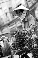 A street vendor with a pile of rambutans on the back of her bicycle.